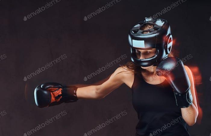 Schöne Brünette weibliche Boxer in Sportbekleidung. Isoliert auf dunklem strukturiertem Hintergrund.