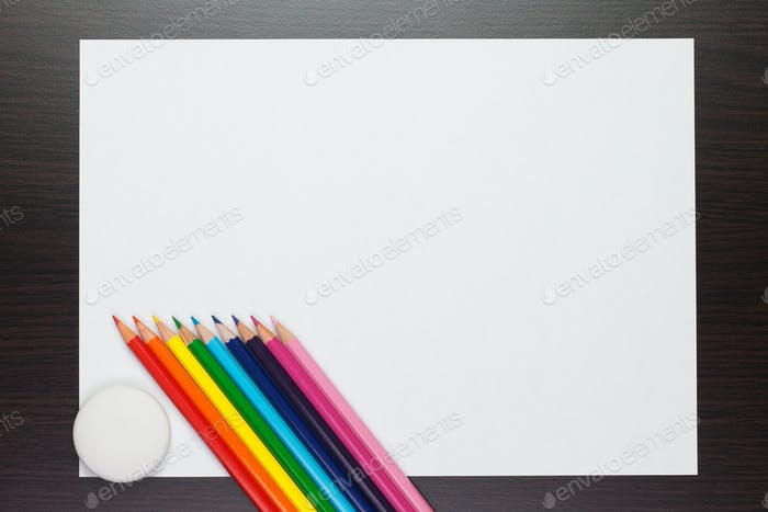 Blank Sheet Of Paper On The Table With Colorful Pencils And Rubb