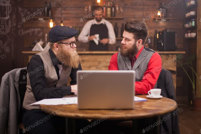 Two handsome businessmen looking at each other while talking about finances in a vintage pub
