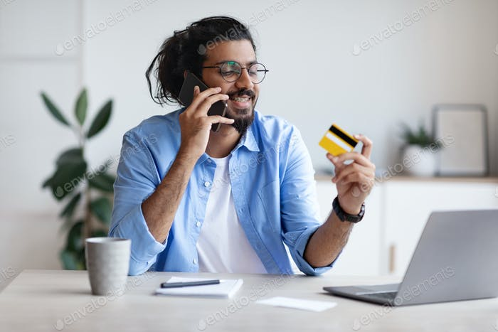 Easy Payments. Indian Freelancer Guy Holding Credit Card And Talking On Cellphone