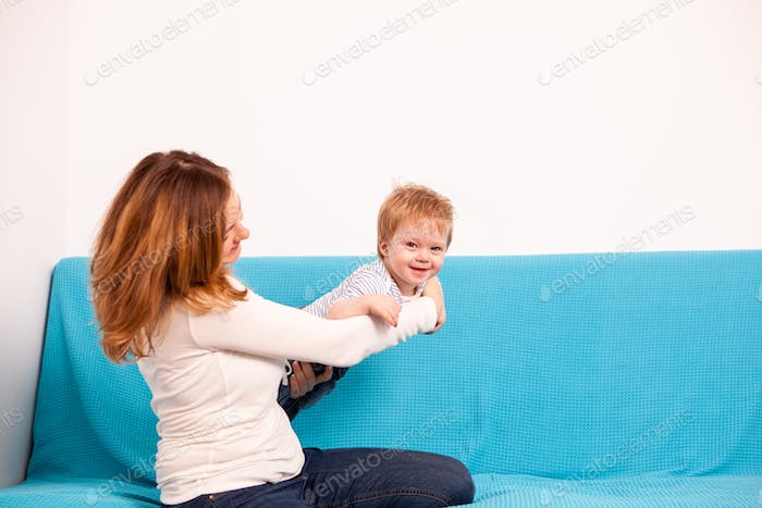 Mother with her son playing on the sofa