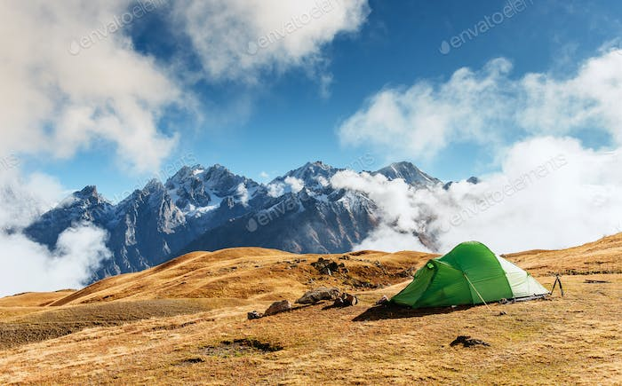 Tent against the backdrop of snow-capped mountain peaks.