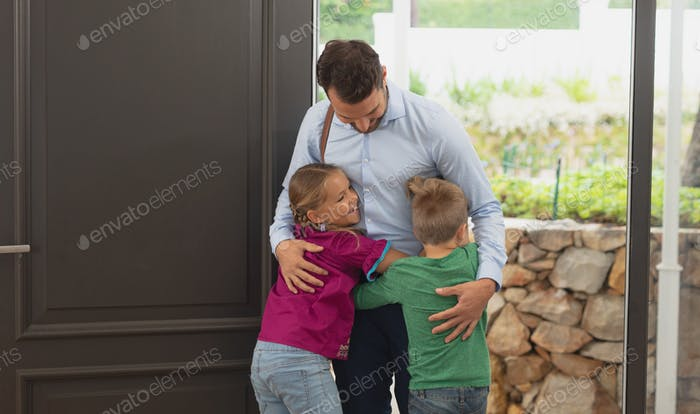 Front view of Caucasian father embracing his two children as he enters the house