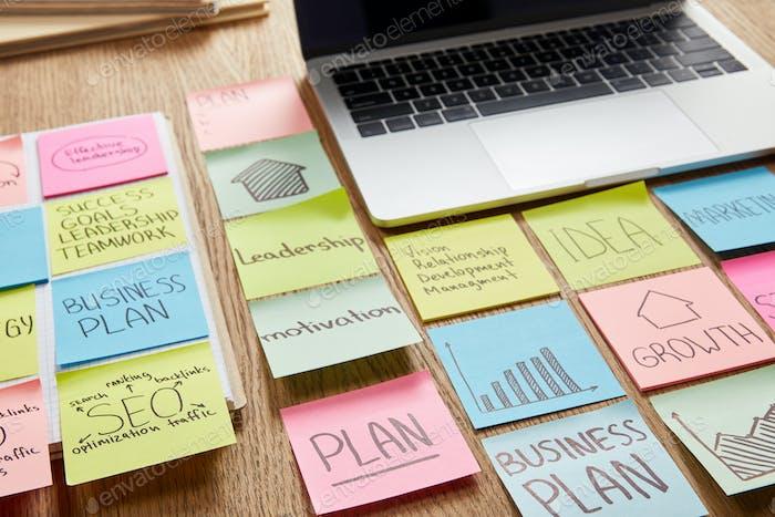 pegatinas de papel de colores con estrategia empresarial y portátil en la mesa