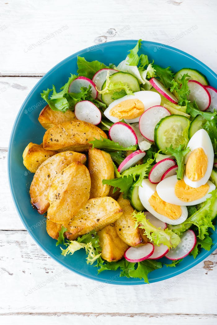 Delicious baked potato, boiled egg and fresh vegetable salad