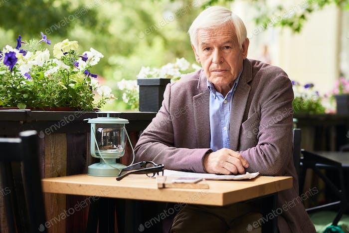 Старший джентльмен Расслабляющий в открытый кафе