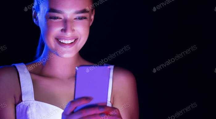 Woman texting on phone, face illuminated by screen light