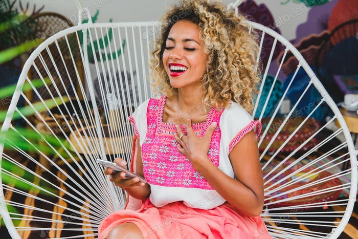 Attractive elegant smiling African American lady with smartphone on chair