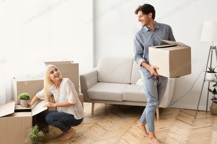 Young Married Couple Unpacking Moving Boxes In New House