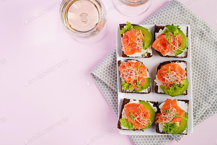 Salmon sandwiches with cream cheese and microgreen. Canape with salmon.Top view. Flat lay