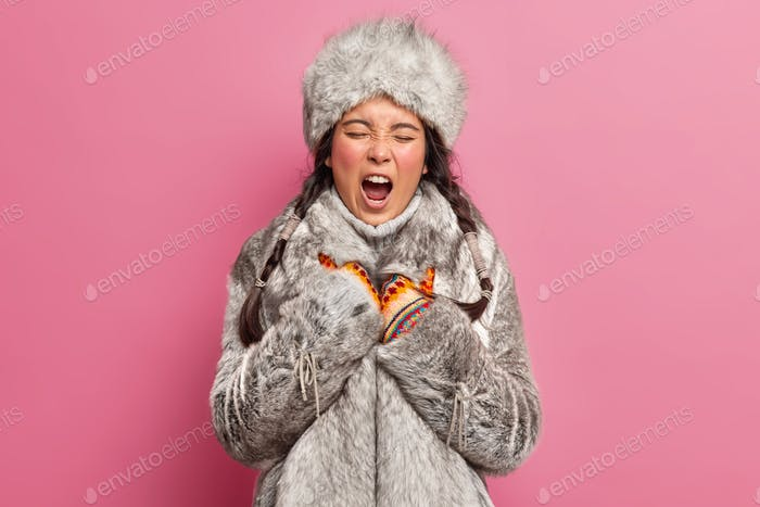 Indigenous circumpolar woman yawns and has sleepy expression wears winter clothes lives at greenland