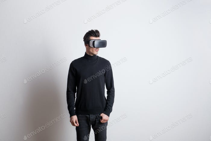 Portrait of a young man with virtual reality goggles in a studio.