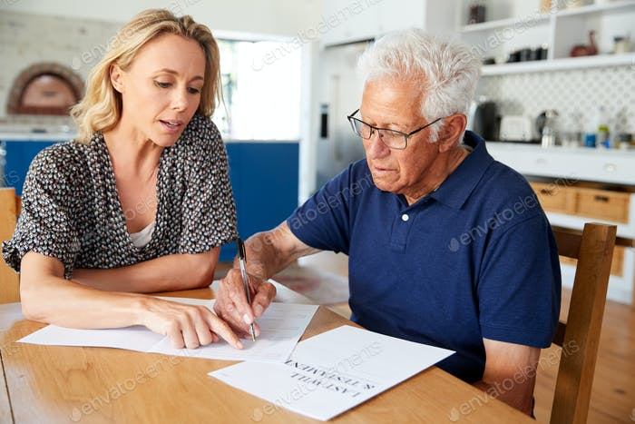 Frau hilft Senior Man, den letzten Willen und das Testament zu Hause zu vollenden