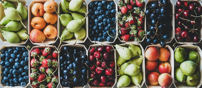 Summer fruit and berry assortment in wooden boxes, top view