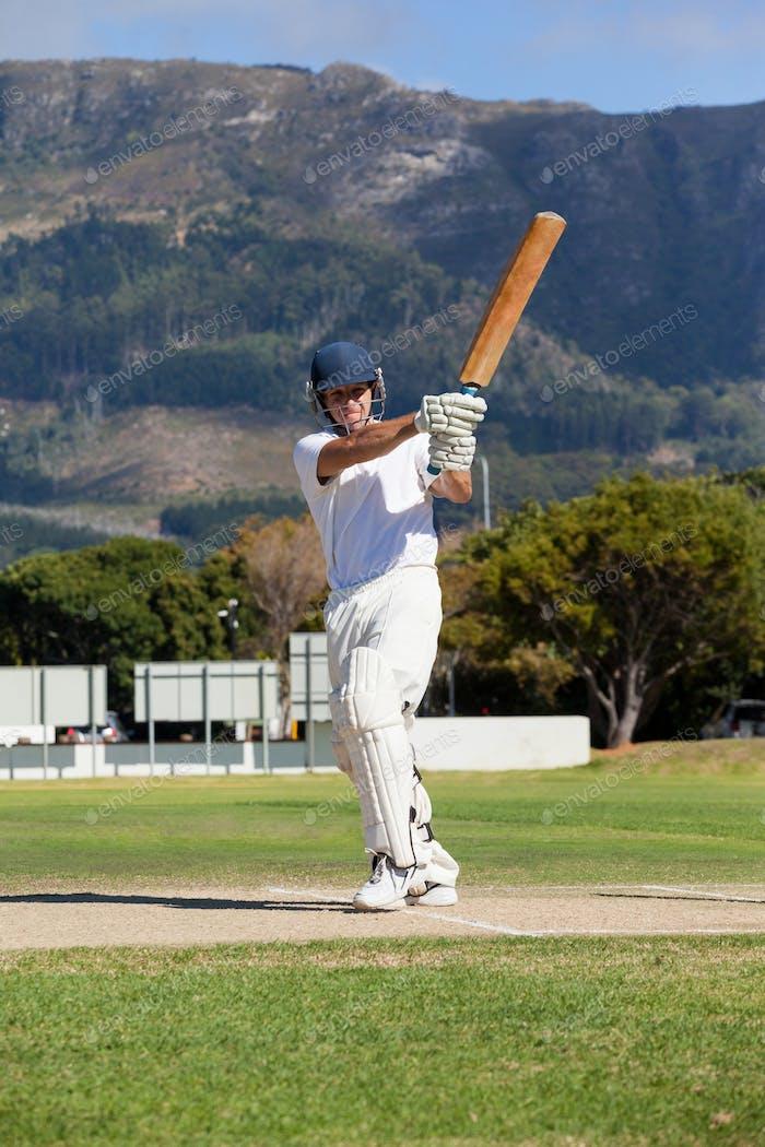 Full length of batsman playing cricket on field