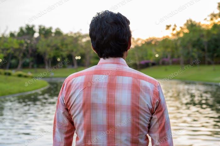 Indian man looking at scenic view of the lake in peaceful green