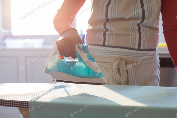 Woman ironing shirt on ironing board in kitchen