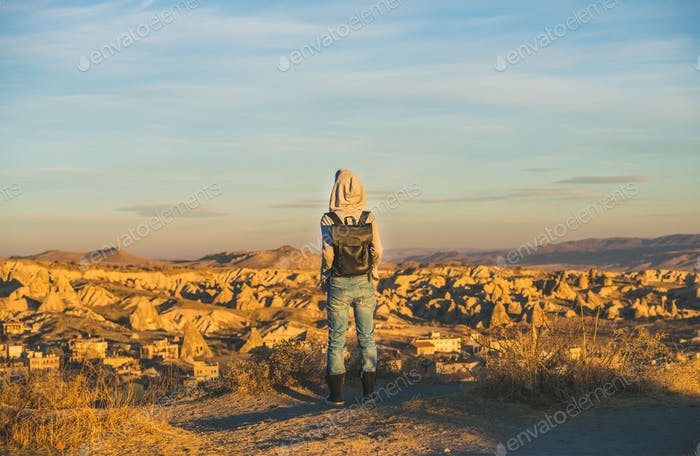 Young woman traveller standing at sunrise, Cappadocia, Central Turkey