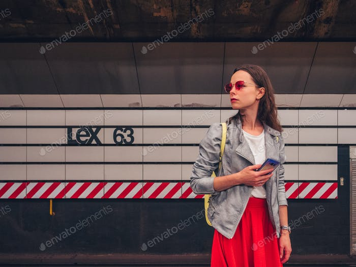 Attractive girl with a phone at a subway station