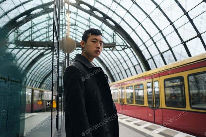 Young stylish Asian businessman in coat confidently looking in camera at subway station