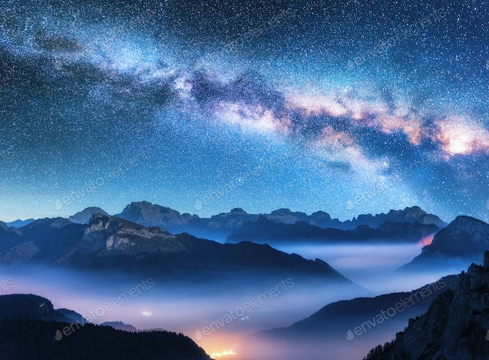 Milky Way above mountains in fog at night in summer