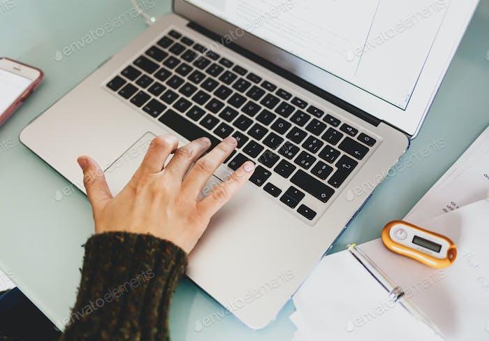 Frau, die mit Laptop-Computer zu Hause arbeitet. Intelligentes Arbeitskonzept.