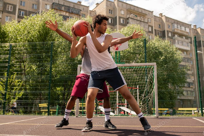 One of basketball players with ball trying not to let his rival take it away