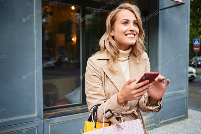 Excited blond girl in stylish trench coat with shopping bags happily using cellphone on city street