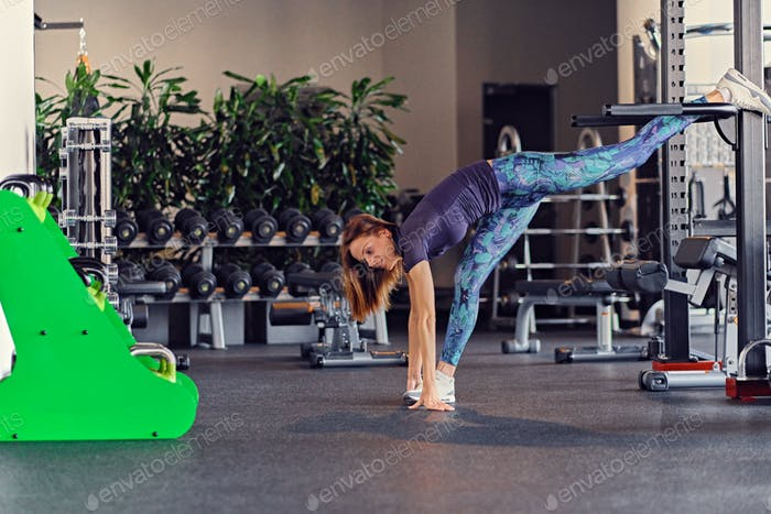Female fitness model stretching in a gym club.