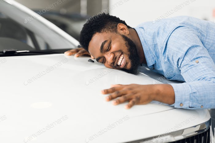 Happy African American Man Hugging New Car In Auto Dealership