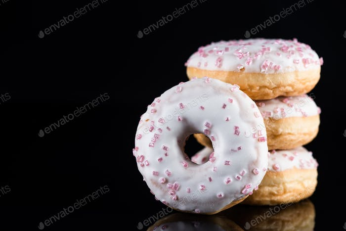 Stack of  White Chocolate Donuts or Doughnuts on Black Background with Copy Space