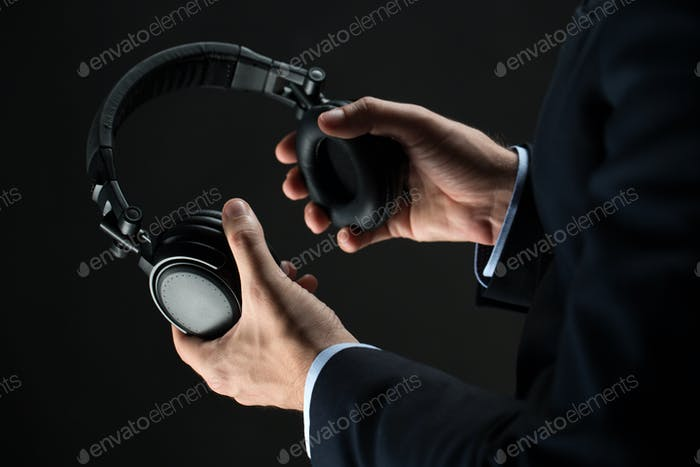 close up of businessman hands holding headphones