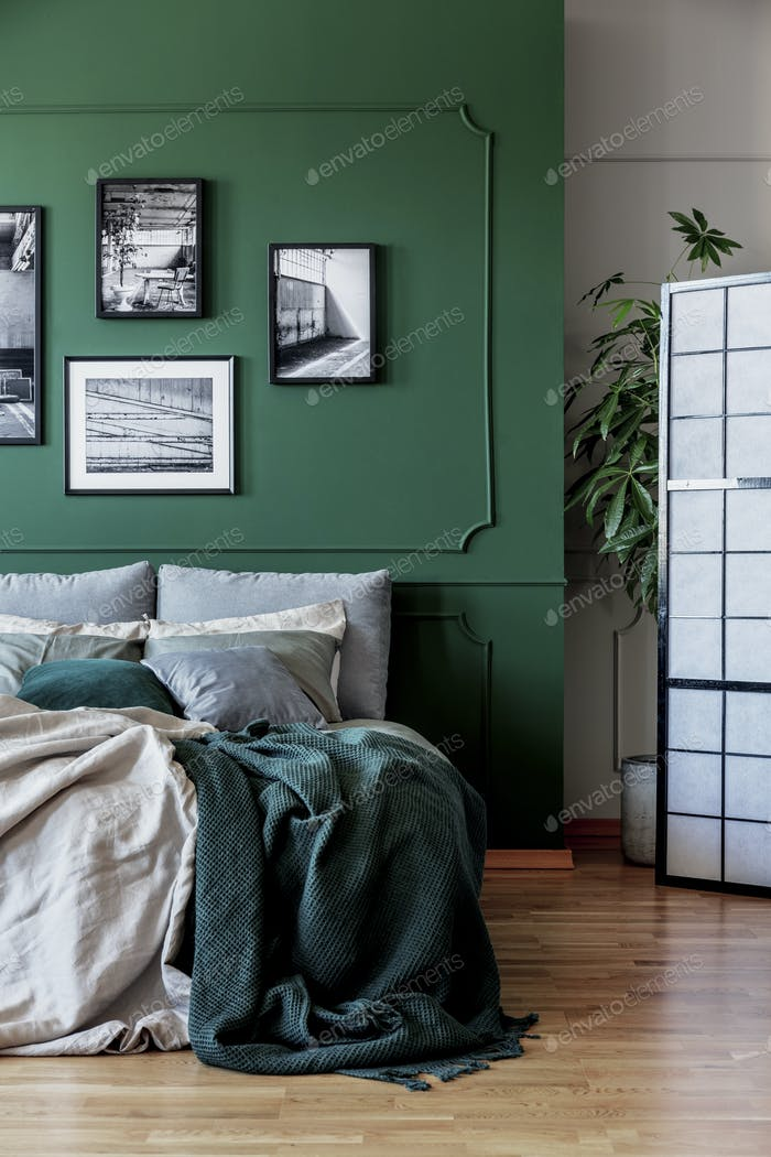 Gallery of black and white posters and photos on emerald green wall in trendy bedroom