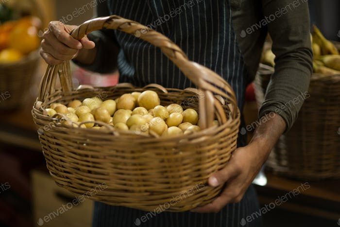 Vendor holding basket of potatoes at the grocery store
