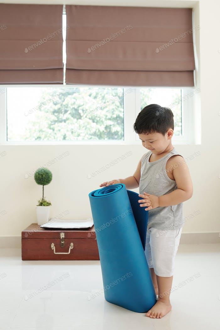 Curious boy with yoga mat