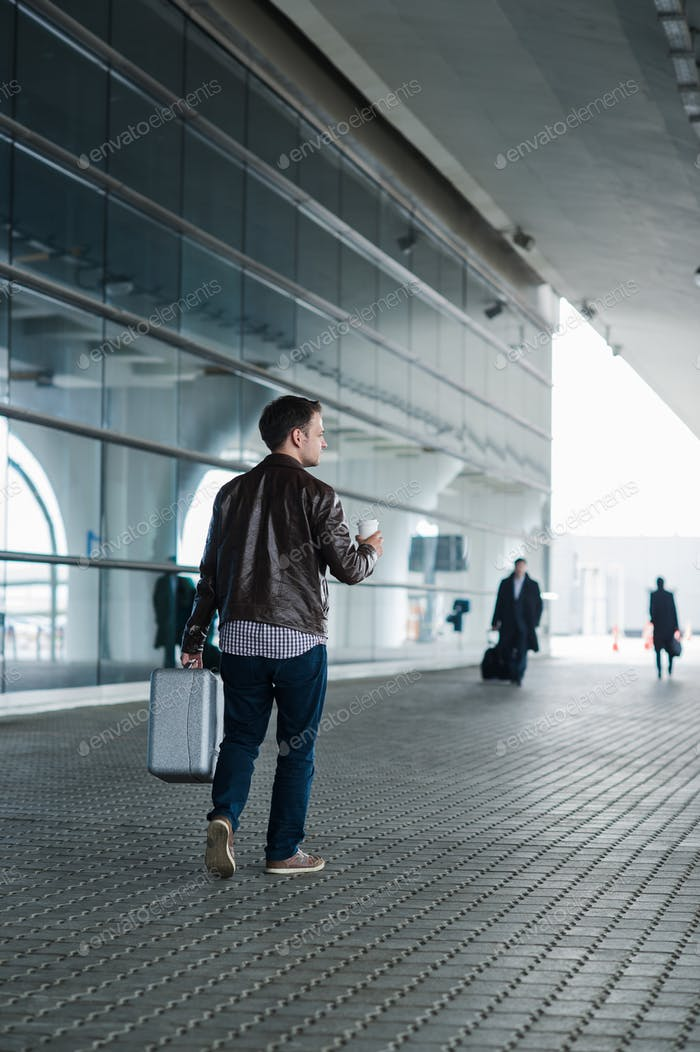 Profile portrait of a young man walking with suitcase and coffee cup near the airport terminal