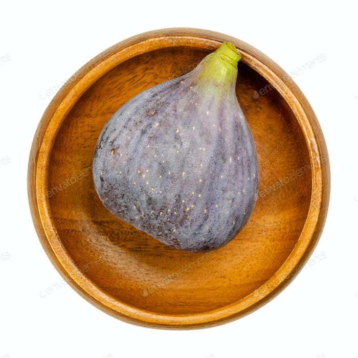 Fresh, ripe and whole fig in a wooden bowl