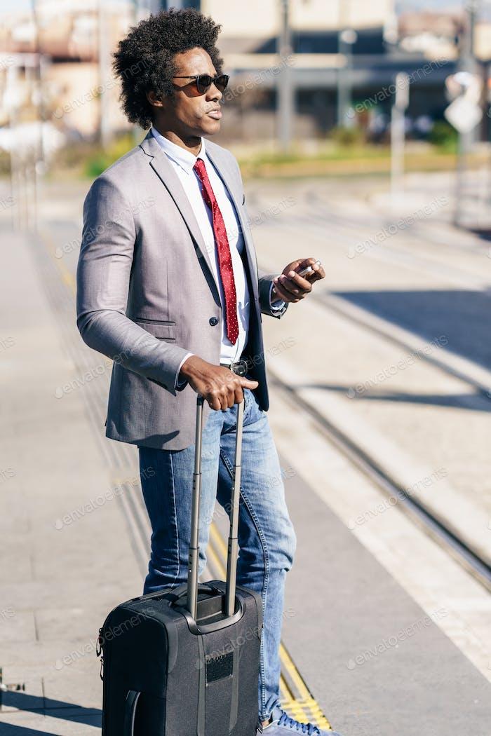 Schwarzer Geschäftsmann wartet auf den nächsten Zug