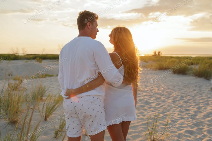 Couple in love in white clothes walking on the beach.