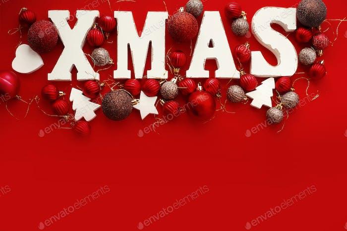 Weihnachts-Holzwort mit roten und goldenen Kugeln Ornamente auf rotem hellem Papier