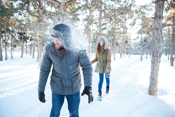 Freudige Frau Aushöhen Schneebälle in gutaussehenden Mann