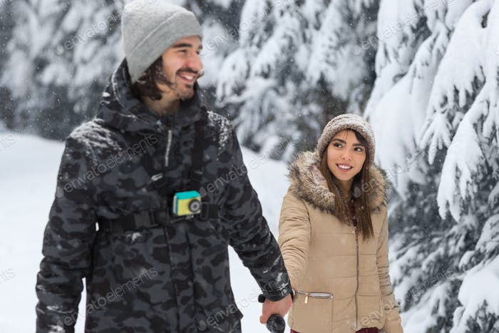 Young Romantic Couple Walking In Snow Forest Outdoor Mix Race man And Woman Holding Hands