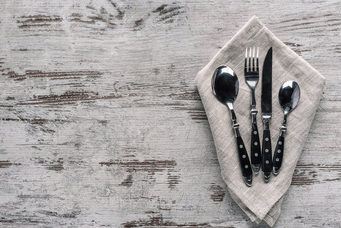 Set of dinner silverware with napkin on wooden table