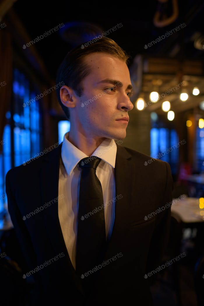 Portrait of young businessman thinking at restaurant
