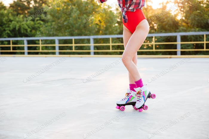Legs of woman in swimsuit skating on roller skates outdoors