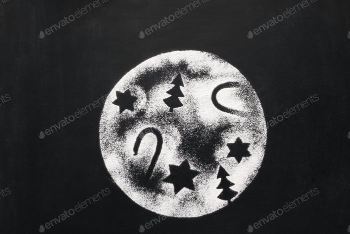 Mond mit Feiertagsfiguren von Zucker auf Kreidetafel