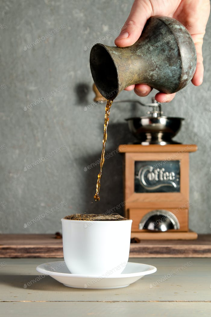 Men Hand Pouring a Cup of Coffee Creating Splash on Wooden Background.
