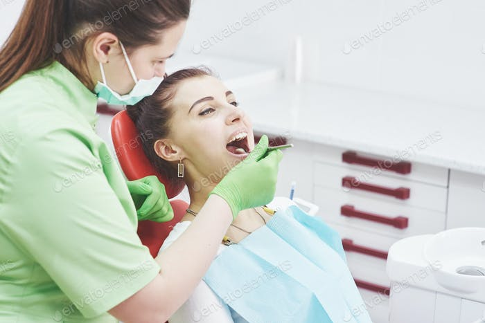 Dentist curing a female patient in the stomatology. Early prevention and oral hygiene concept
