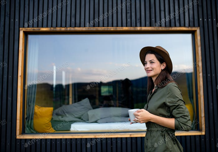 Young woman outdoors, weekend away in container house in countryside