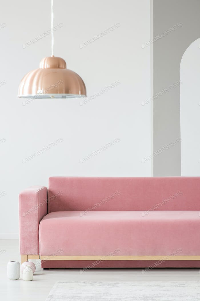 Copper lamp above pink settee in minimal white living room inter